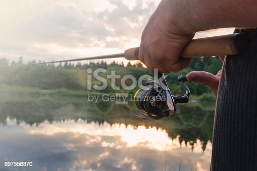 The man catches a fishing-rod fish on a reservoir.