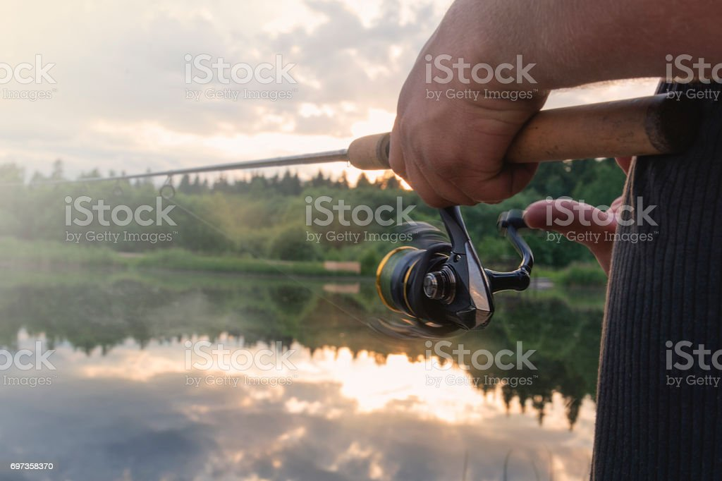 The man catches a fishing-rod fish on a reservoir. stock photo