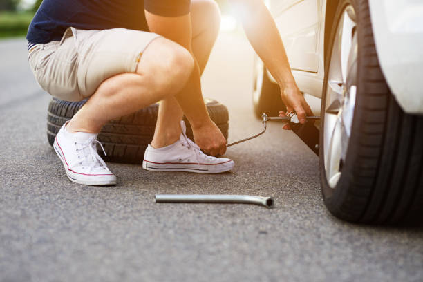 The man changes the tire on his car stock photo