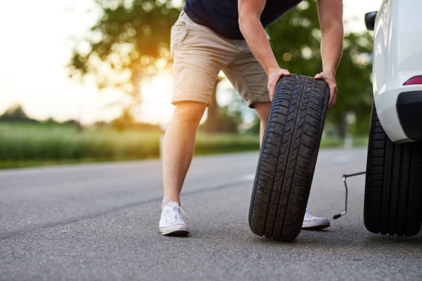 The man changes the tire to a broken car on the road stock photo