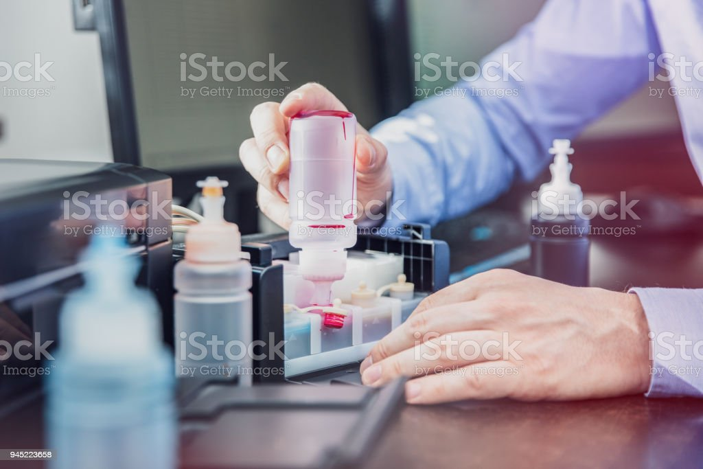 The man completes the ink container in his printer stock photo
