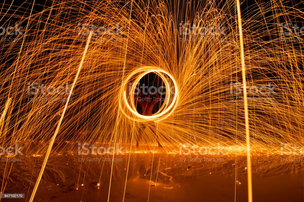 The man dacing swing fire Show on the beach in the Island of Thailand. stock photo