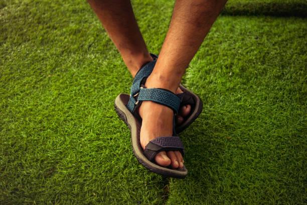 os pés do homem usando sandálias esportivas. foco seletivo - sandália - fotografias e filmes do acervo