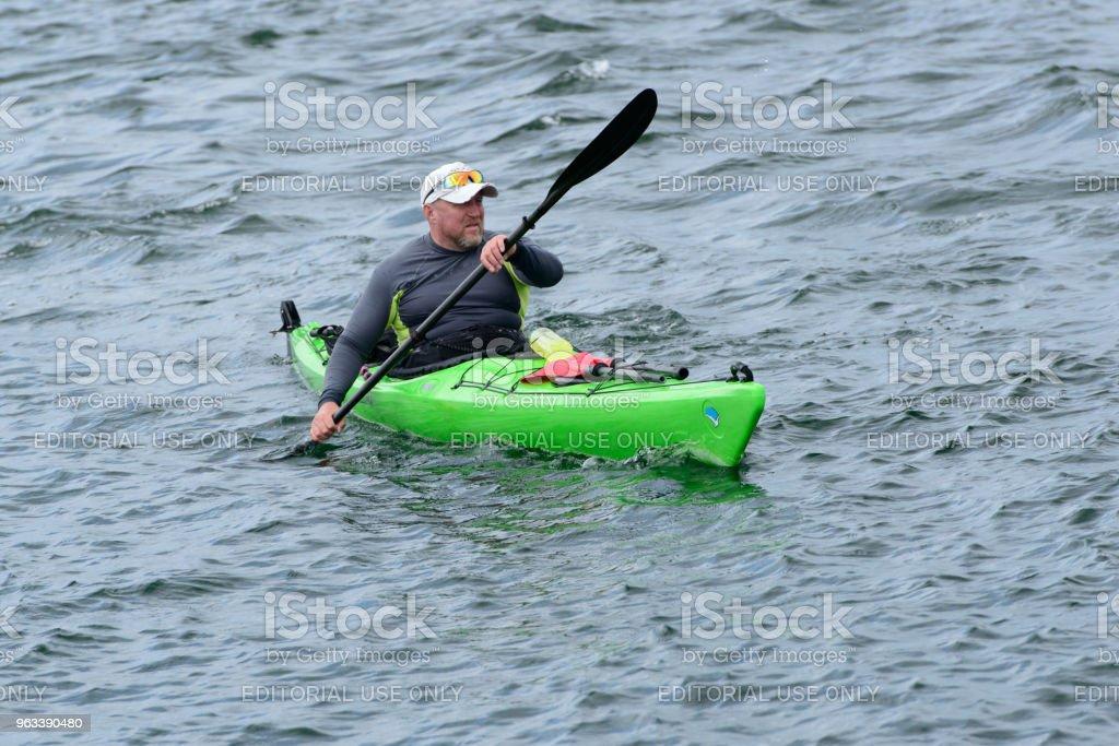 The man floats on the green kayak. - Zbiór zdjęć royalty-free (Aktywny tryb życia)