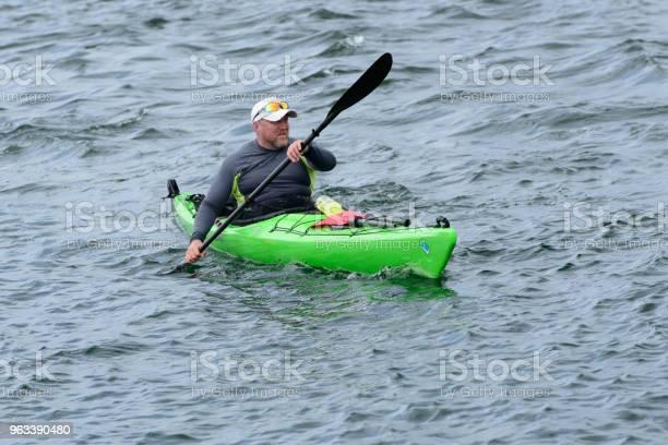 Mężczyzna Unosi Się Na Zielonym Kajaku - zdjęcia stockowe i więcej obrazów Aktywny tryb życia