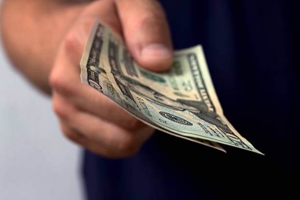 The man gives money. Hand holding out cash. stock photo