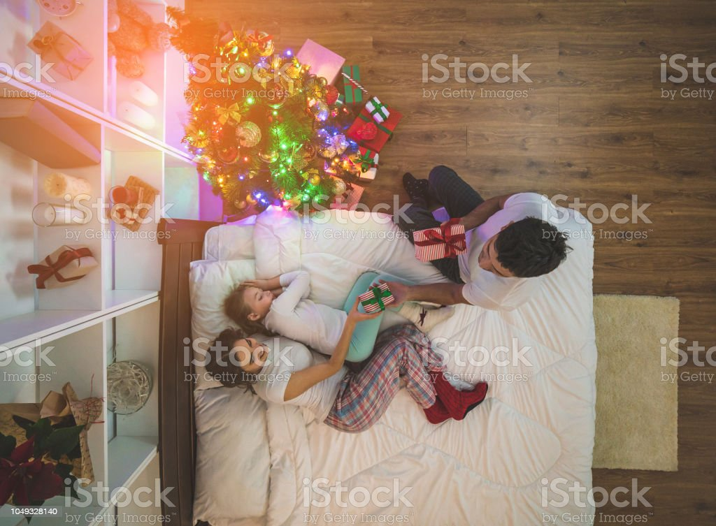 The Man Giving Gifts To His Family On The Bed Night Time View From