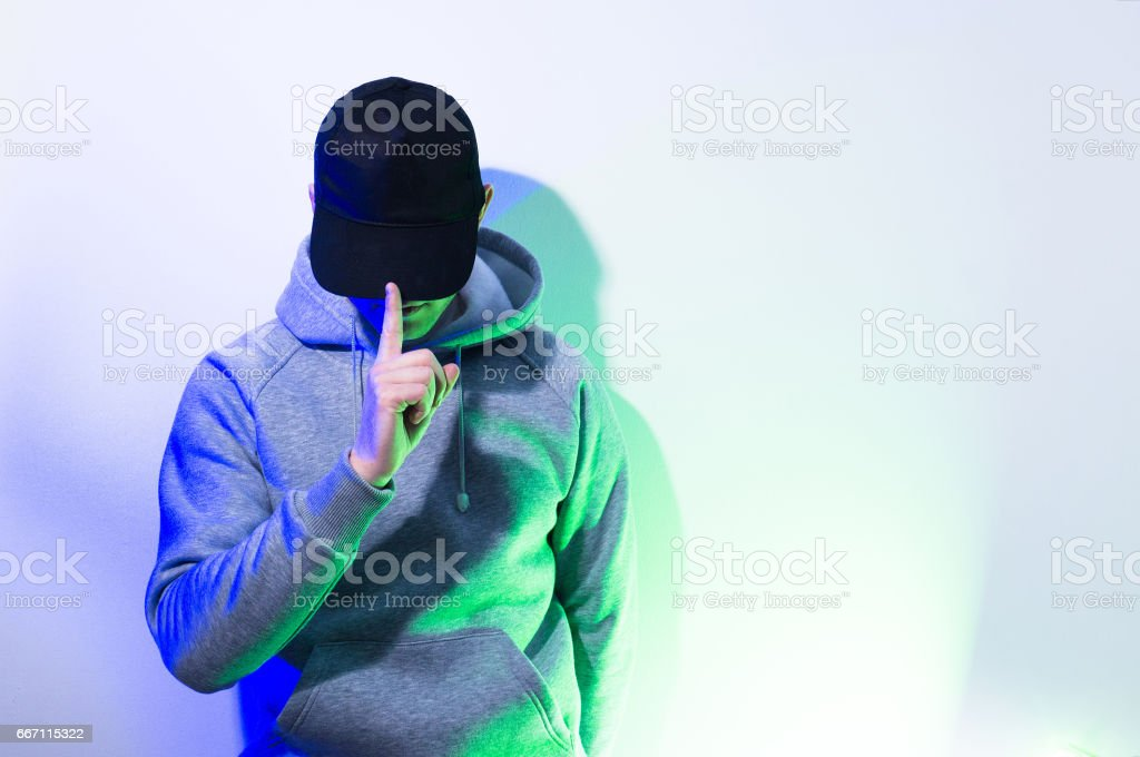 the man, guy in the blank black , baseball cap, grey hoody,  on a white background, mock up, free space, logo presentation , template for print,  design stock photo