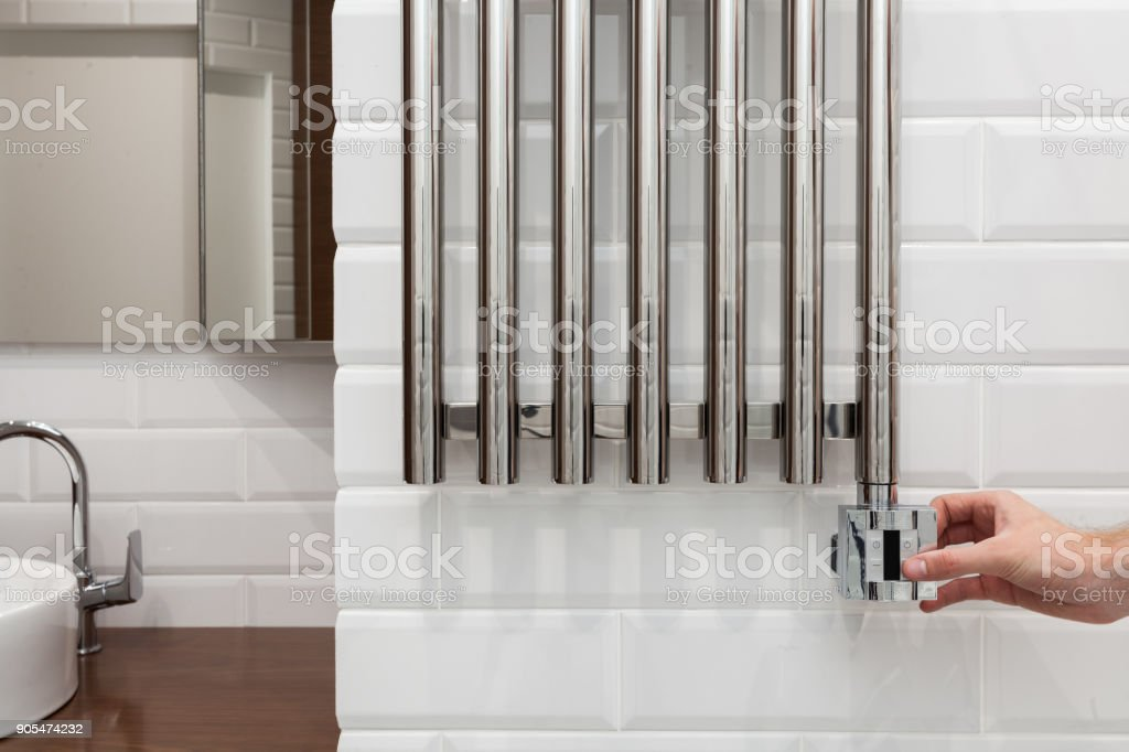 The man hand regulates the temperature in the heated towel rail. stock photo