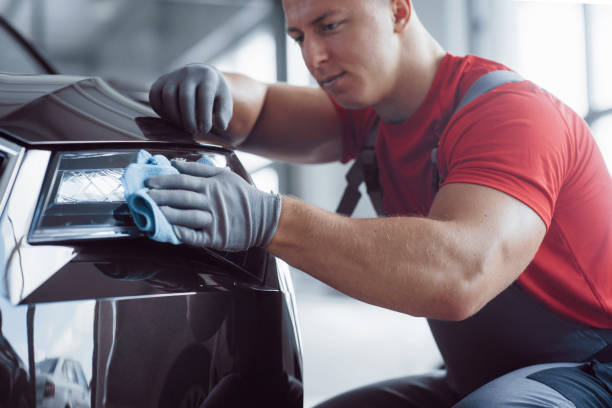 the man holds the microfiber in hand and polishes the car. the new machine is being prepared for sale - close up auto foto e immagini stock