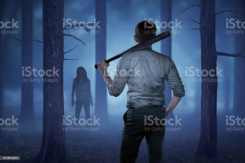The man in a bloody shirt holding a bloody stick stock photo