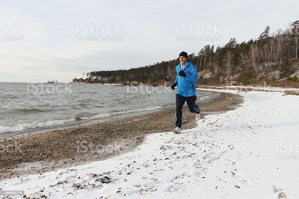 The man in a blue jacket running on snow stock photo