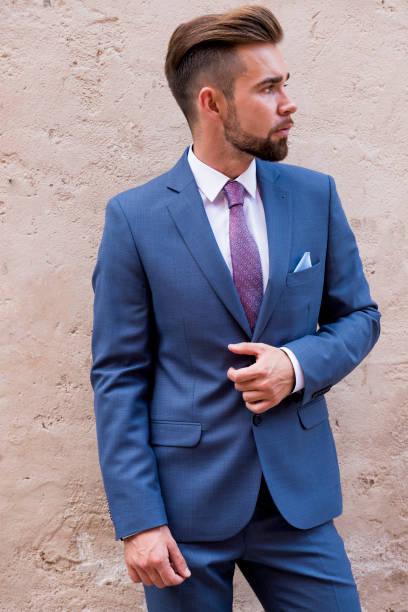 der mann in einem grauen festliche anzug posiert vor dem hintergrund einer alten mauer - bräutigam anzug vintage stock-fotos und bilder
