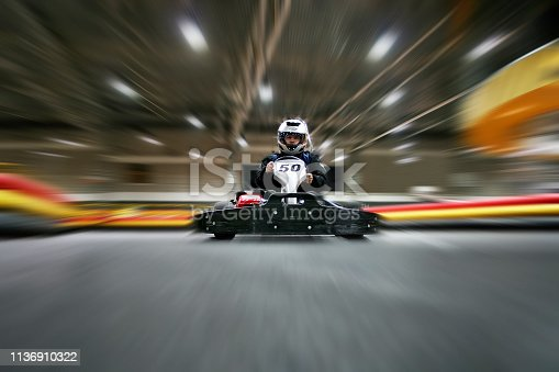 The man in a helmet in the go-kart moves on a karting track