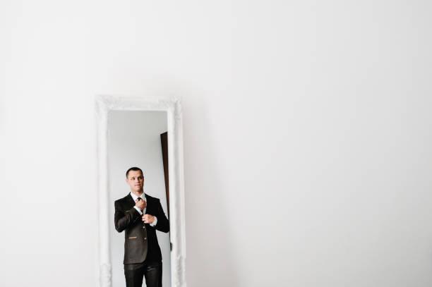 der mann im anzug schaut auf seine spiegelung im spiegel und richtet krawatte auf hemd zu hause aus. kleiderkonzept. vorbereitung auf ein geschäftstreffen. - bräutigam anzug vintage stock-fotos und bilder