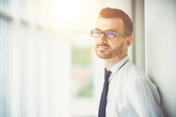 the man in glasses stand near the column in the office on the sun background - man look sky scraper foto e immagini stock
