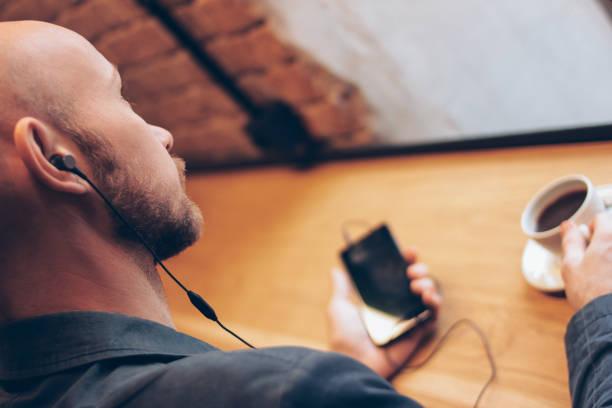 de man in een koptelefoon met behulp van mobiele telefoon, zittend met koffie in café - podcast stockfoto's en -beelden