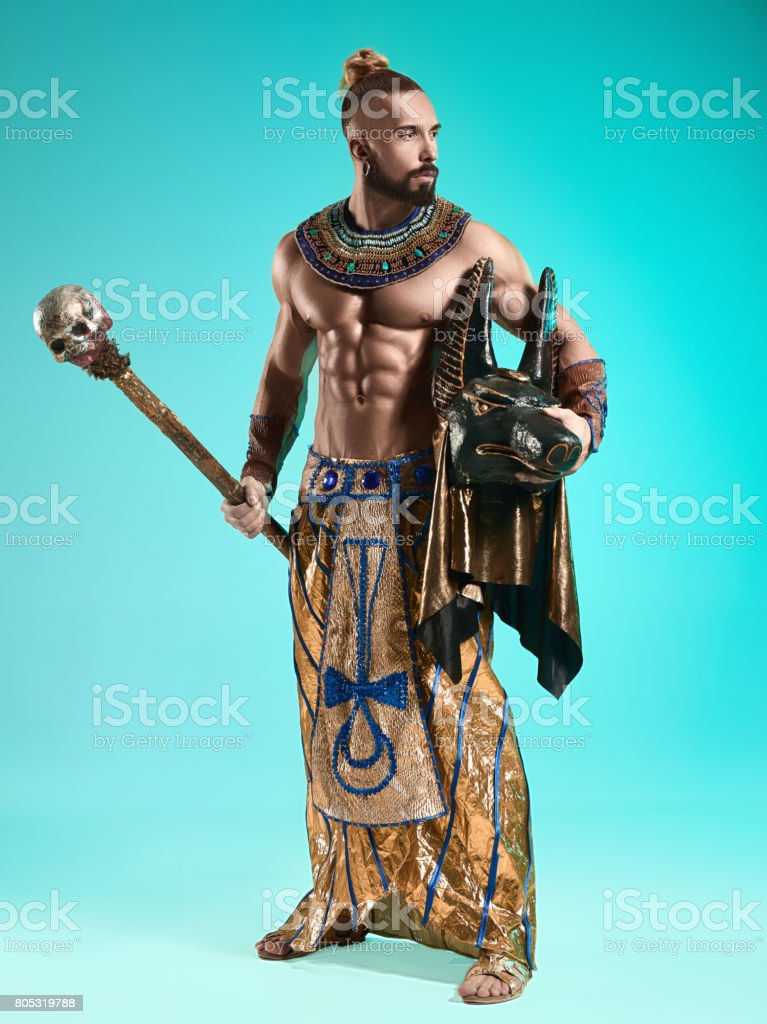 The man in the image of the ancient Egyptian Pharaoh with a mask of Anubis on his face on blue background stock photo