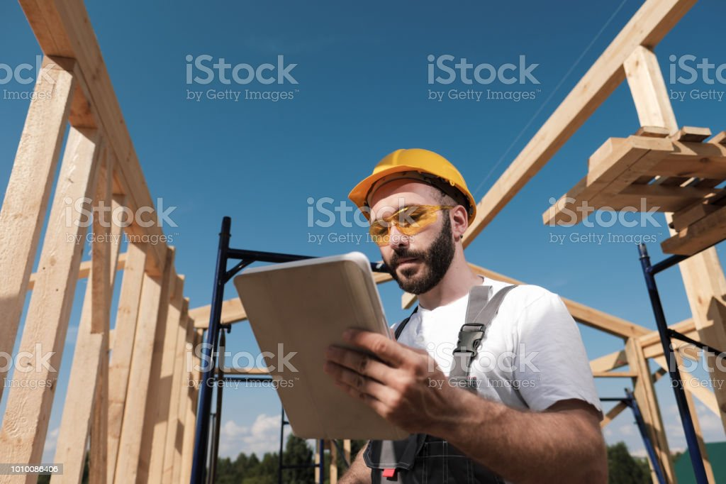 The man is a builder on the background of the roof of a frame house,...