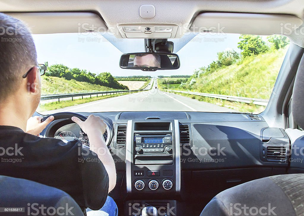 The man is driving with hands on the steering wheel. stock photo
