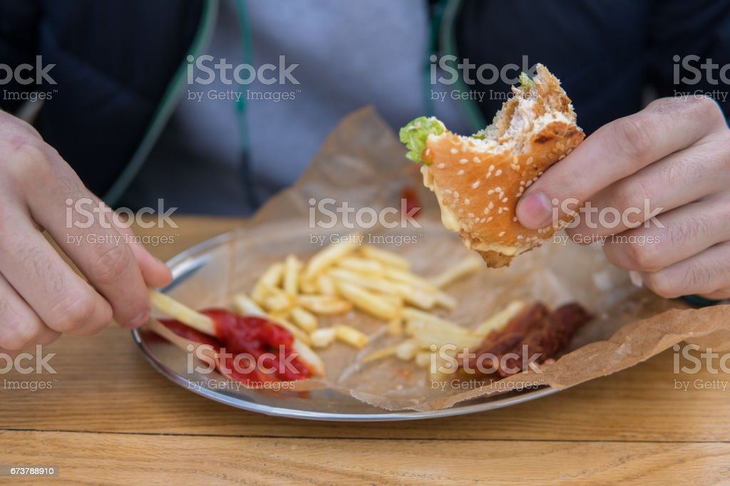 L'homme est de manger un hamburger dans un restaurant de rue de fast food photo libre de droits
