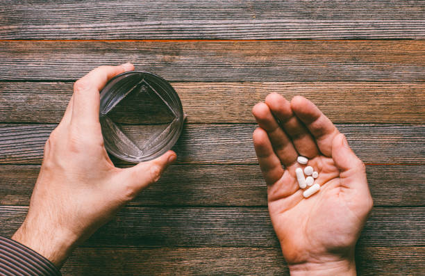 the man is going to eat pills and capsules and drink with water, the top view - sleeping pill stock photos and pictures