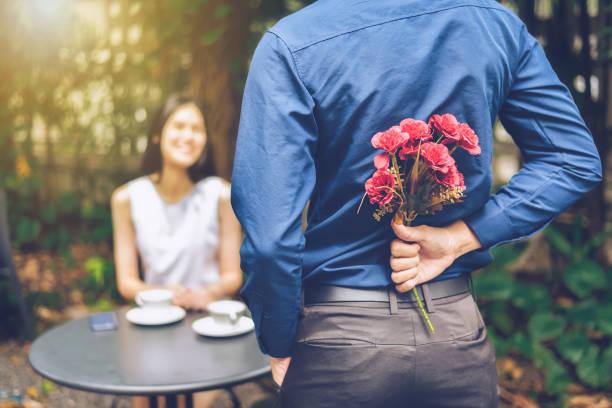 o homem está escondendo as flores vermelhas atrás dele para surpreender sua namorada. - mulher flores - fotografias e filmes do acervo