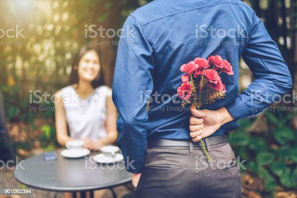 The Man Is Hiding Red Flowers Behind Him In Order To Surprise His Girlfriend Stock Photo - Download Image Now