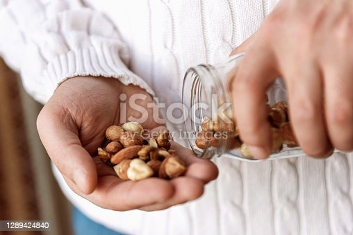 istock The man is holding a jar of walnuts hazelnuts and almonds 1289424840