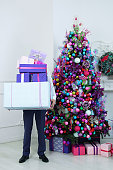 The man is holding boxes with gifts. Standing next to the Christmas tree.