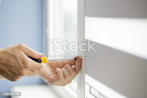 The man is repairing the plastic window.
