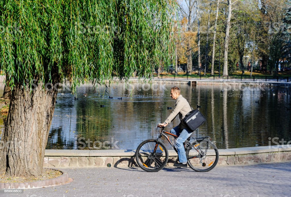 The man  is ridding on the bicycle. stock photo