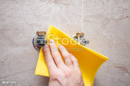 istock The man is rubbing the tile and the water taps on the wall in the bathroom 931671512