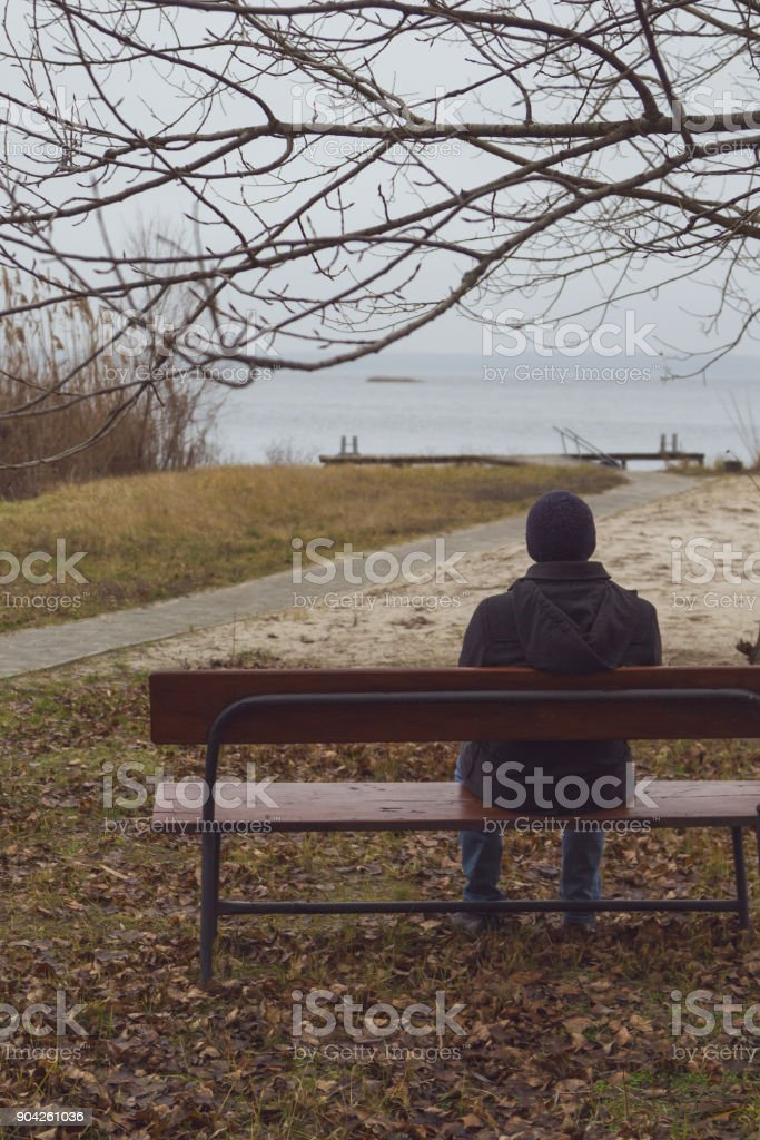 The man is sitting on the bench and looking at the river. stock photo