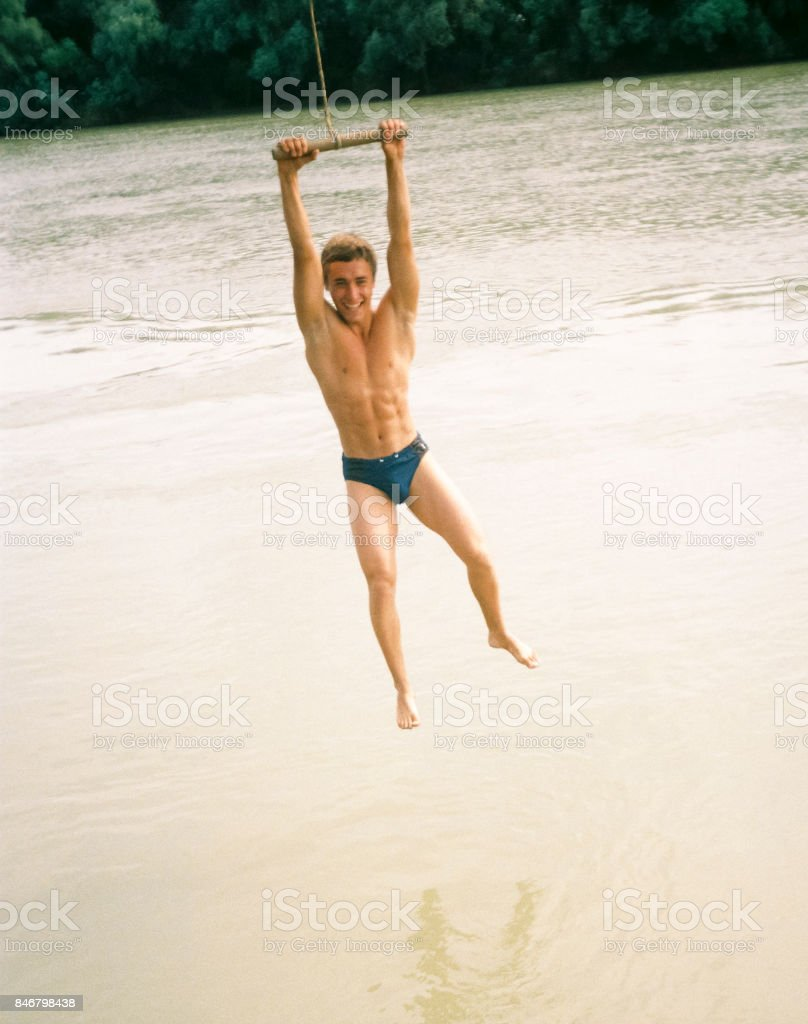 The man is swinging on the tarp. Jumping from the stream on the river bank. stock photo