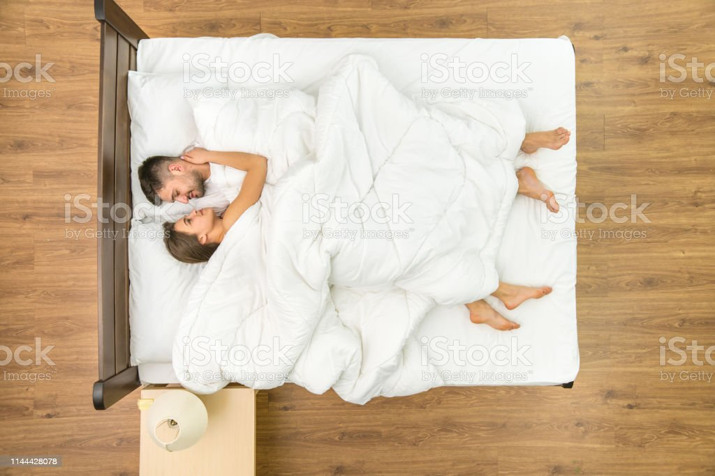 The man lay near a woman on the bed. View from above