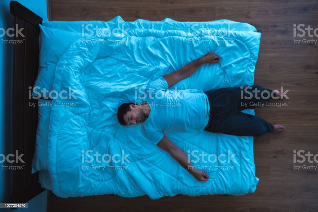 The man laying on the bed. view from above, evening night time The man laying on the bed. view from above, evening night time Above Stock Photo