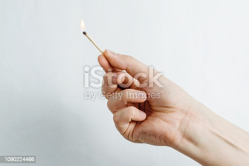 istock The man lights a match on a bright gray background. 1090224466