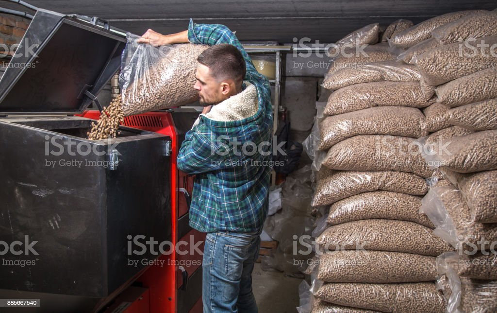 the man loads the pellets in the solid fuel boiler, economical heating stock photo