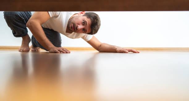 yatağın altında görünen adam - aranmak stok fotoğraflar ve resimler