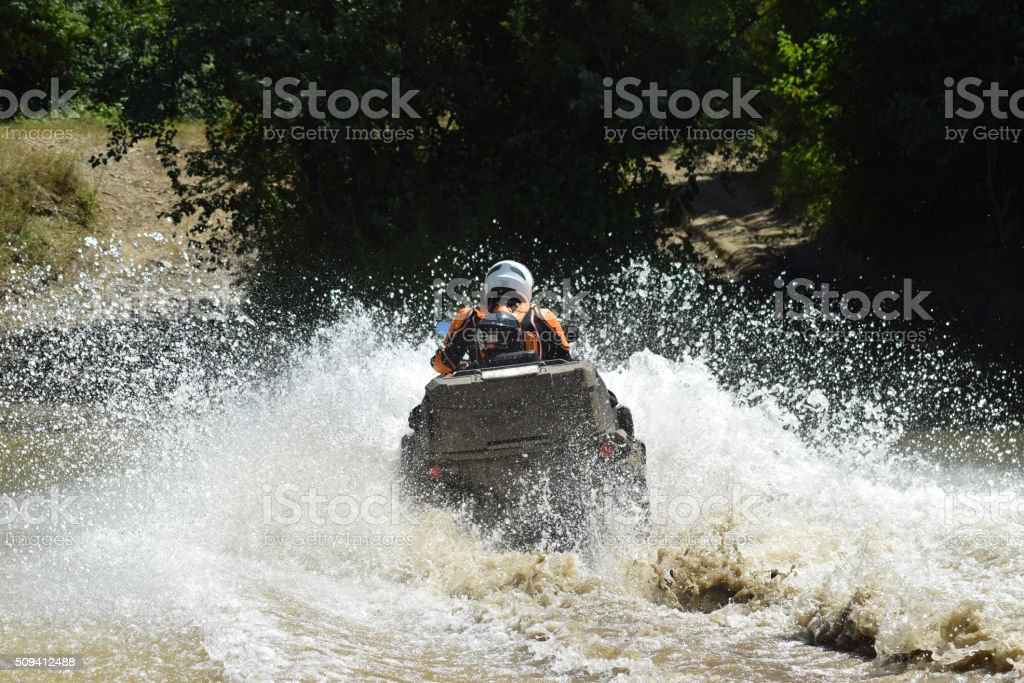 The man on the ATV crosses a stream stock photo