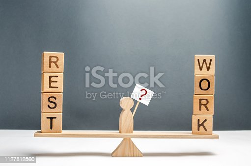 1175869940 istock photo The man on the scales with a poster and a sign of questions. The choice between work and rest. Concept of the right balance. lifestyle in harmony, overtime at work and grueling work. Exhausting. 1127812560