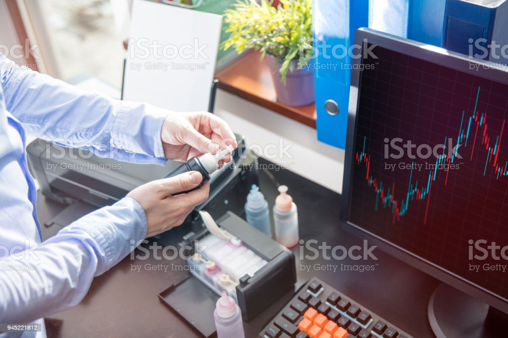The man opens the container with the black ink for the printer stock photo