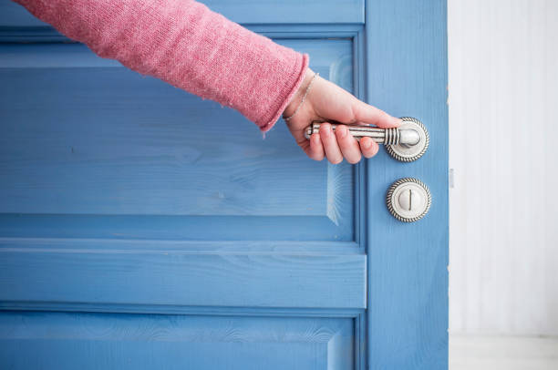 The man opens the door blue man holding a metal pen in an open wooden door blue entering stock pictures, royalty-free photos & images