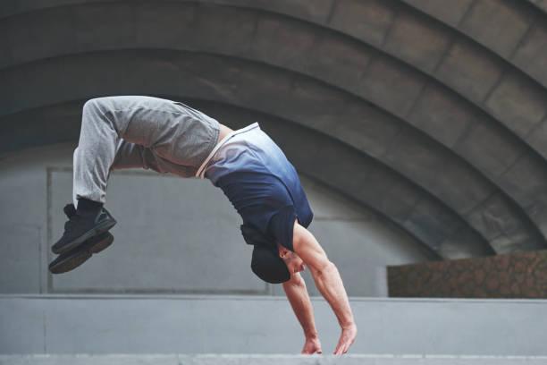 Der Mann im Freien praktiziert Parkour, extreme Akrobatik. – Foto