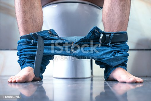 1045838148 istock photo The man pants down  is sitting in the toilet. Diarrhea. 1139860757