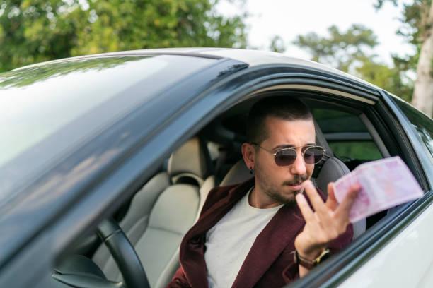 Der Mann zahlt das Geld. Junger Geschäftsmann streckt Geld aus Autofenster – Foto