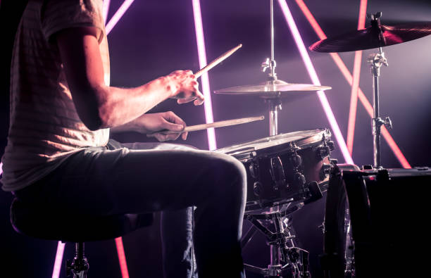 The man plays the drums against the background of colored lights and picture id955534292?b=1&k=6&m=955534292&s=612x612&w=0&h= r9azaysikhptcsbvhgmalkl h9onz1bvogg5n7ey54=