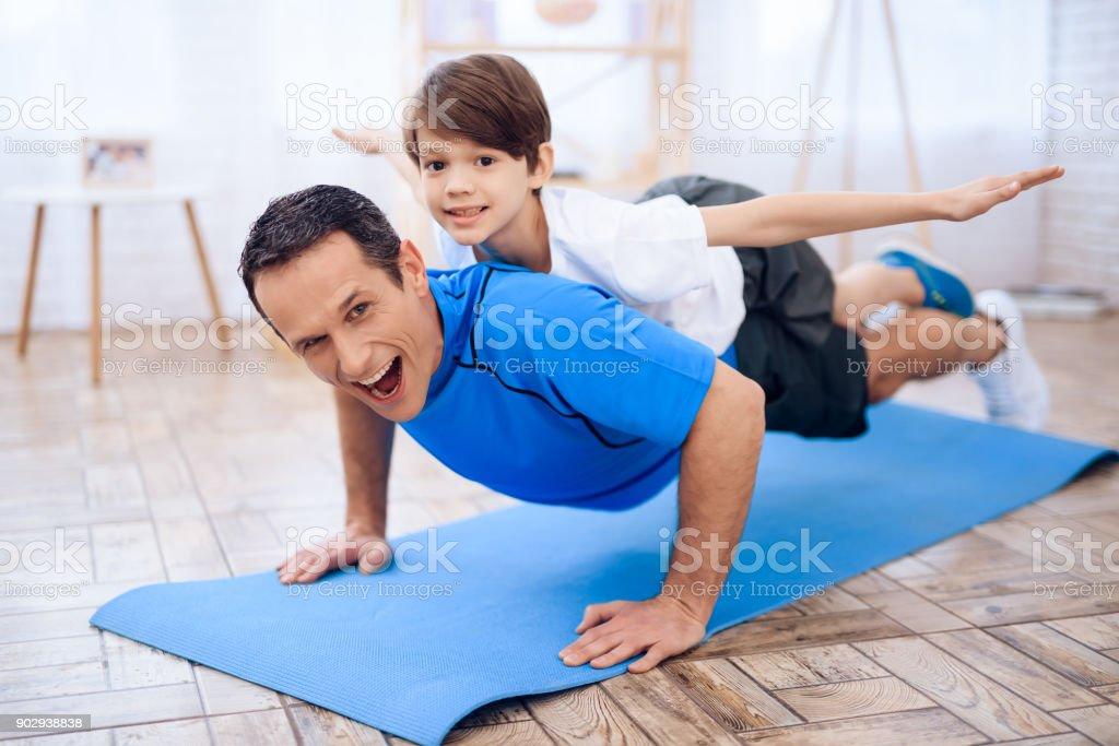 Der Mann Pushup vom Boden mit dem jungen auf dem Rücken. – Foto