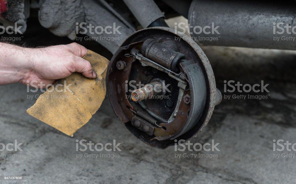 Der Mann Reparatur Bremse Schlagzeug für Auto und reinigt Bremsbeläge mit Sandpapier. – Foto